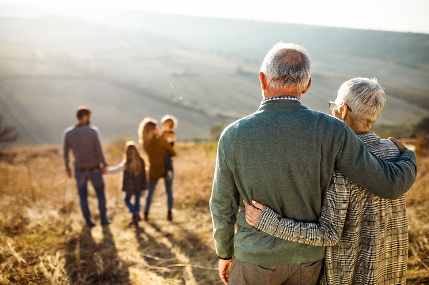 Elderly man and woman observing family