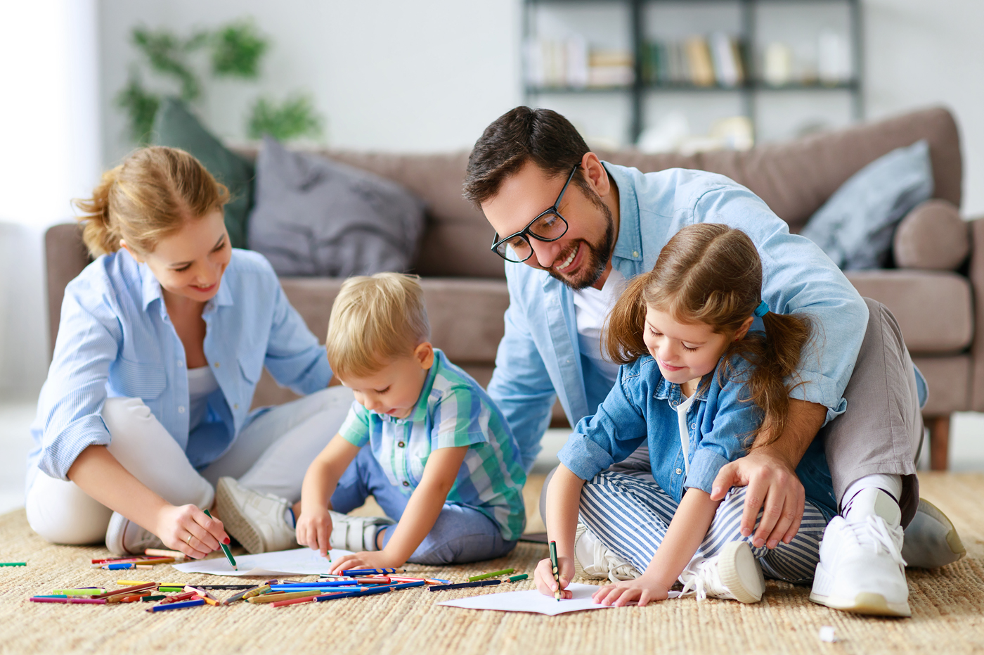 Family sitting on floor of home coloring